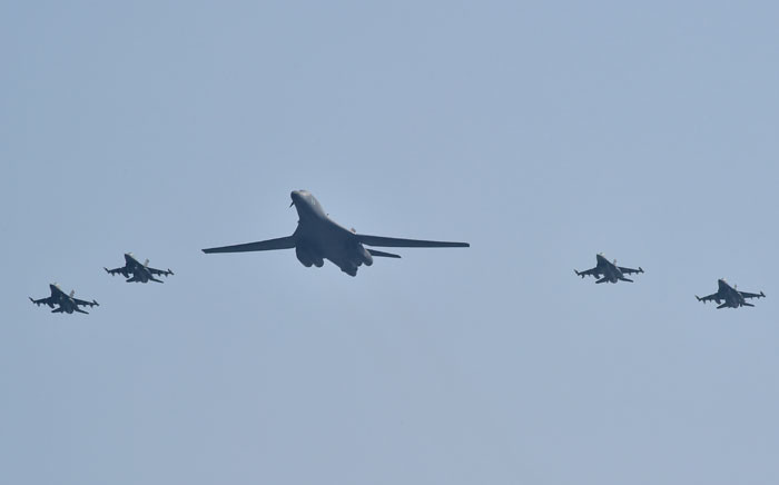 A US B-1B Lancer (C) is escorted by US F-16 fighter jets as it flies over the Osan Air Base, aiming at reinforcing the US commitment to its key ally in Pyeongtaek on 13 September 2016.