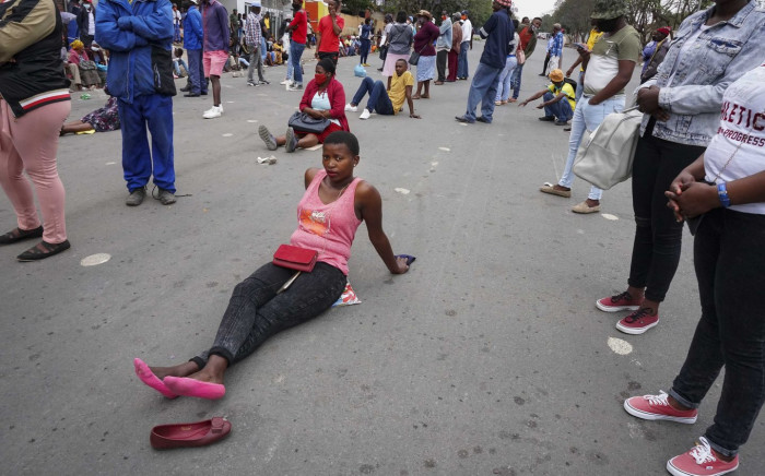 24 October 2020: Eastern Cape resident Esihle Xelo, who hails from Mqanduli, sits on Durham Street outside the Mthatha Post Office waiting for the Covid-19 social relief of distress grant. She travels more than 40km each month to collect the R350. Picture: Bonile Bam / New Frame