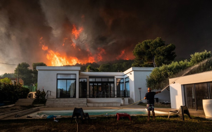 A man uses a garden hose to drench his house before being evacuated as a wild fire burns in the background, in La Couronne, near Marseille, on 4 August  2020. Picture: AFP