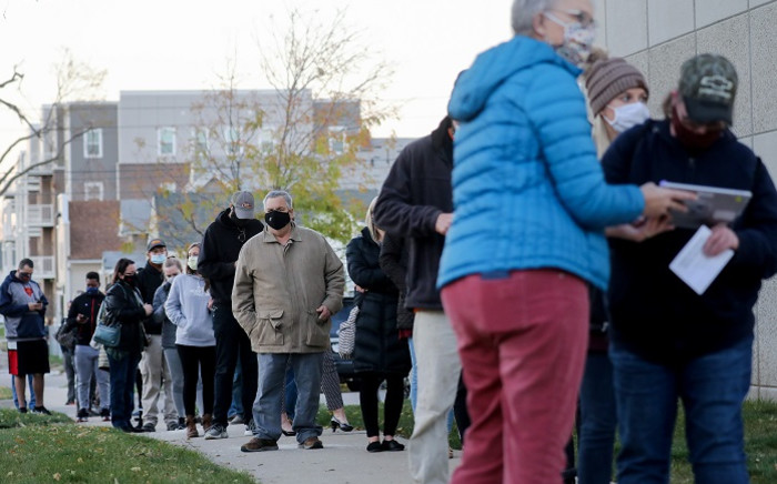 An election official (3rd R) confirms voter information as voters wait in line to cast their ballots on the final day of early voting for the 2020 presidential election on 2 November 2020 in Cedar Rapids, Iowa. Picture: AFP.