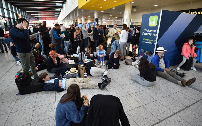 Passengers wait at the North Terminal at London Gatwick Airport, south of London, on 20 December 2018 after all flights were grounded due to drones flying over the airfield. Picture: AFP.
