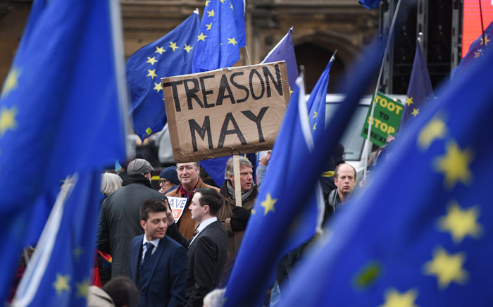 A protester with an anti-Theresa May placard is seen amid other protesters with EU flags outside the Houses of Parliament in central London on 15 January 2019.