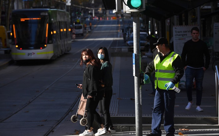 FILE: A cleaner (R) wipes down a pole in Melbourne's central business district on 17 June 2020, as more Australians return to the city centre with a relaxing of the COVID-19 coronavirus rules. Picture: AFP.