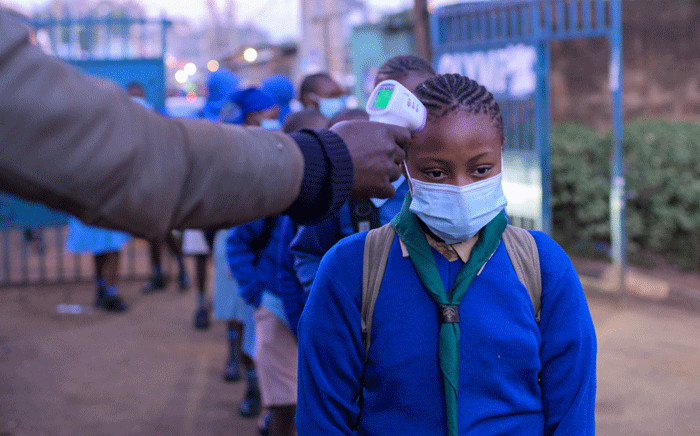 Students of Olympic Primary School wait in a line to have their temperatures measured at the entrance of the school in the early morning of the official re-opening day of public schools on January 4, 2021, in Kibera slum, Kenya, as students return to school following a nine-month closure ordered by the government in March 2020 to curb the spread of the COVID-19 coronavirus.  Picture: AFP.