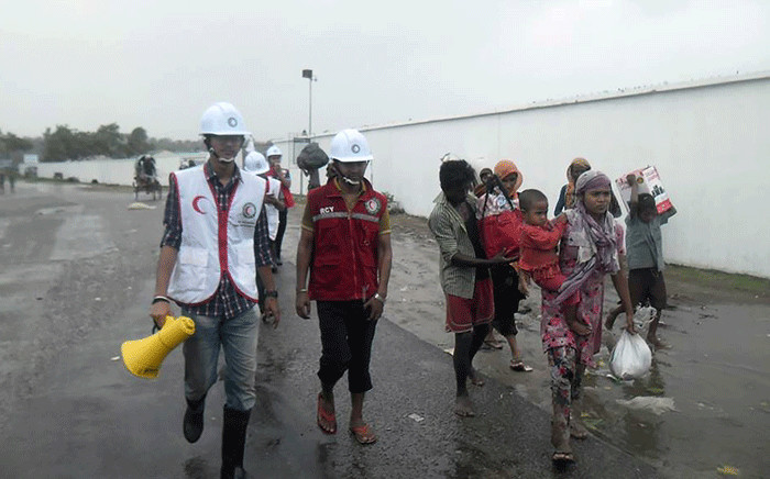 FILE: This handout photo released by the Bangladesh Red Crescent organisation shows volunteers helping residents move to safe locations before Cyclone Roanu made landfall in coastal Bangladesh in Cox's Bazar on 21 May 2016. Picture: AFP