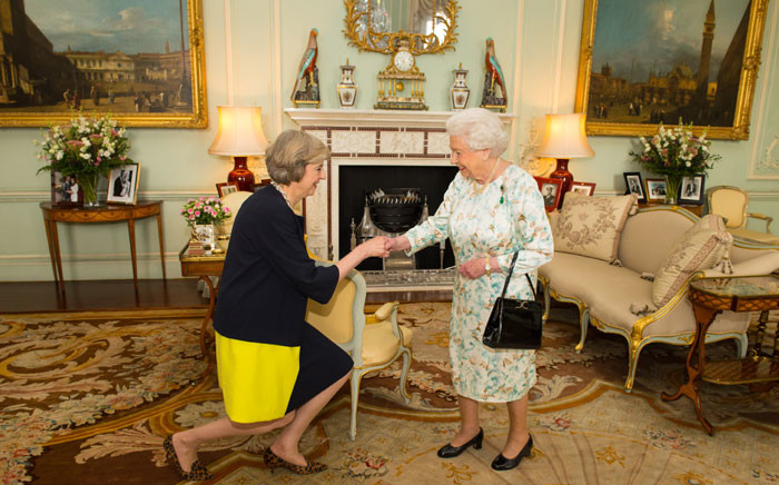 The new leader of the Conservative Party Theresa May (L) kneels as she is greeted by Britain's Queen Elizabeth II (R) at the start of an audience in Buckingham Palace in central London on July 13, 2016 where the Queen invited the former Home Secretary to become Prime Minister and form a new government. Theresa May became Britain's second female prime minister on July 13 charged with guiding the UK out of the European Union after a deeply devisive referendum campaign ended with Britain voting to leave and David Cameron resigning. Picture: AFP.