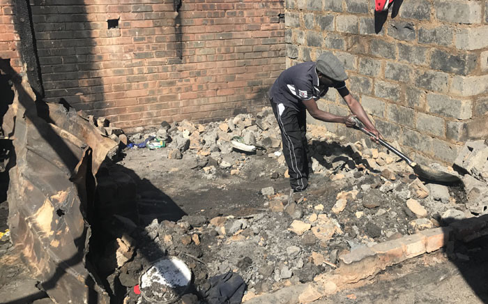 Residents of Alexandra try to salvage what's left of their belongings, after a fire that left at least 120 families homeless and killed a 16-month-old baby boy. Picture: Kgothatso Mogale/EWN.