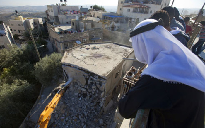 FILE: Palestinian Rafet Dabash looks at a bulldozer destroying his own home in the east Jerusalem district of Sur Baher on November 30, 2012 after an Israeli court ruled that the house was built without a municipality permit. Picture: AFP.