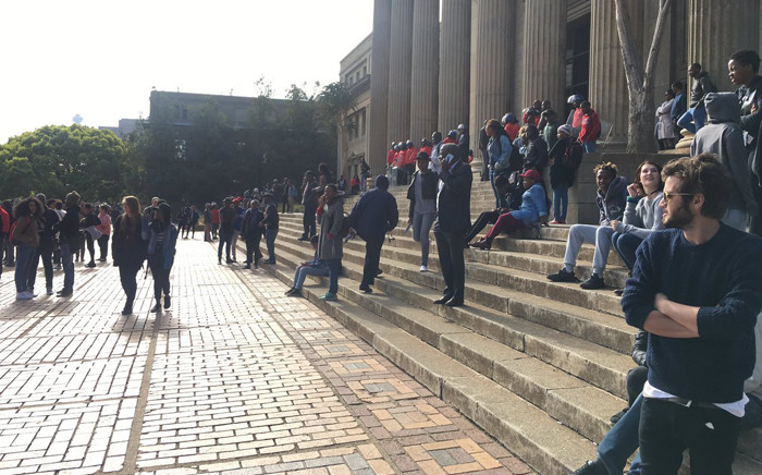 """""""Students outside Wits University Great Hall look on as police move to restore calm after stun grenades were fired when some students refused to be moved away on 4 October 2016. Picture: Clement Manyathela/EWN."""