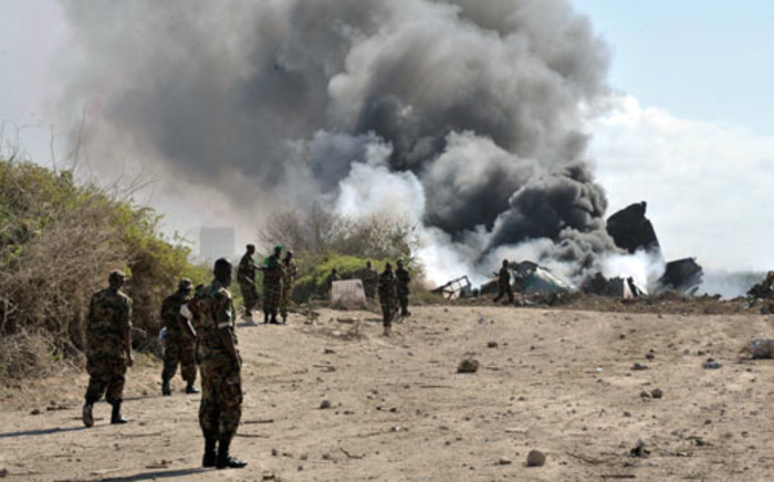 SOMALIA, Mogadishu: soldiers watch as a plane an Ethiopian Air Force aircraft burns after it crashed upon landing at Mogadishu's Aden Adde International Airport. Two of the six crew members survived the crash. Picture: AFP