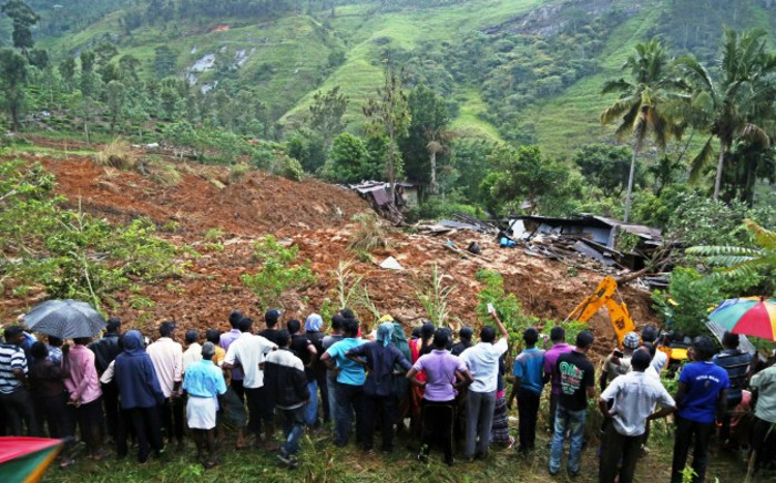The landslide area being excavated by a bulldozer as people watch during rescue operations at Meeriyabedda, Haldummulla in Badulla 218 kms towards the interior from Colombo, Sri Lanka, 29 October 2014. Picture: EPA/M.A.PUSHPA KUMARA.