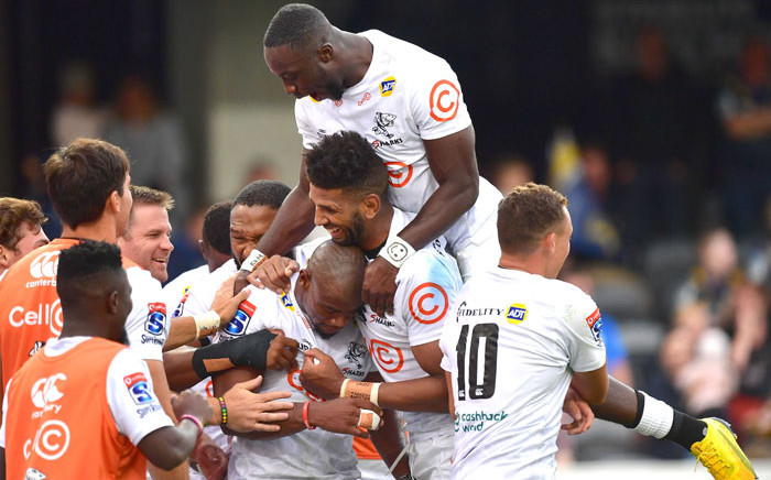 The Sharks' Madosh Tambwe (top) with teammates Hyron Andrews (centre R), Makazole Mapimpi (C) and Curwin Bosch (R) celebrate a try during the Super Rugby match against the Highlanders at the Forsyth Barr Stadium in Dunedin on 7 February 2020. Picture: AFP