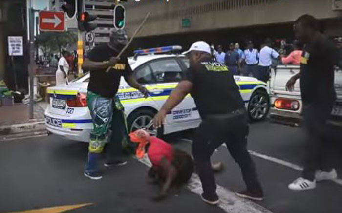 A screengrab of ANC member Thabiso Setona (R) assaulting a woman during protests outside Luthuli house.
