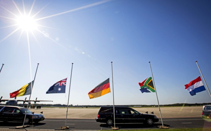 A convoy of hearses carrying coffins containing the remains of victims of the downed Malaysia Airlines flight MH17 drive past flags flying at half-mast in the Netherlands, 23 July 2014. Picture: AFP.