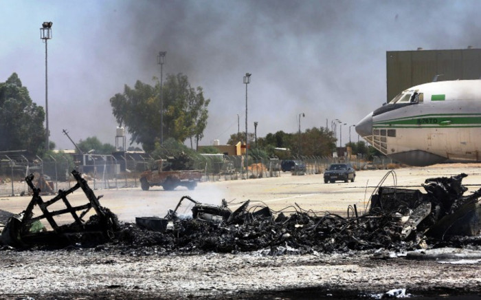 FILE: A picture taken on 16 July 2014, shows the remains of a burnt plane at the Tripoli international airport in the Libyan capital. Picture: AFP.