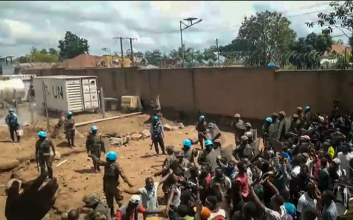 FILE: This frame grab taken from video footage shows crowds as they confront UN peacekeepers in a UN compound on the outskirts of the eastern DRC town of Beni on 25 November 2019. Protesters stormed the camp angered by failures to curb a notorious armed group that killed eight civilians overnight.