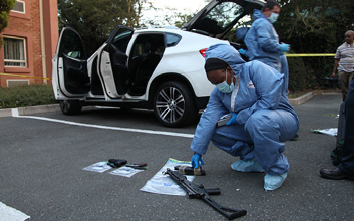 A forensic detective inspects a firearm taken from a murder conspiracy suspect's vehicle at a Road Lodge in Rivonia, 9 January 2014. Picture: Vumani Mkhize/EWN.