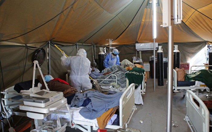 A professional healthcare worker wearing personal protective equipment (PPE) treats a patient in a tent dedicated to the treatment of possible COVID-19 coronavirus patients, while another cleans the ward at the Tshwane District Hospital in Pretoria on 10 July 2020. Picture: AFP