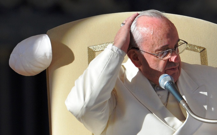 FILE: The wind lifts the skull cap of Pope Francis as he addresses the crowd during his general audience at St Peter's square on 10 December, 2014 at the Vatican. Picture: AFP.