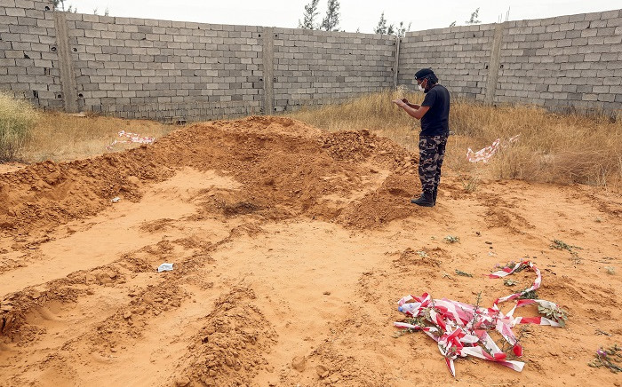 A member of security forces affiliated with the Libyan Government of National Accord (GNA)'s Interior Ministry takes a picture as he stands at the reported site of a mass grave in the town of Tarhuna, about 65 kilometres southeast of the capital Tripoli on 11 June 2020. Picture: AFP