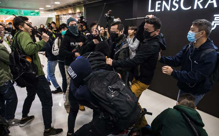 Plainclothes police officers (with batons) clash with pro-democracy protesters during a rally inside a shopping mall in Sheung Shui in Hong Kong on 28 December 2019. Hong Kong has been battered by more than six months of protests that has upended the financial hub's reputation for stability and helped tip the city into recession. Picture: AFP.