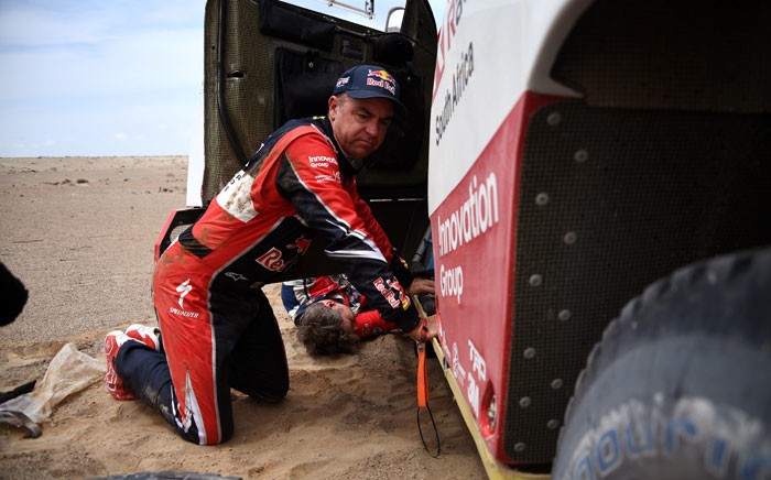 FILE: Toyota's driver Giniel De Villiers of South Africa kneels next to his car after stopping due to technical problems during Stage 3 of the Dakar 2019. Picture: AFP
