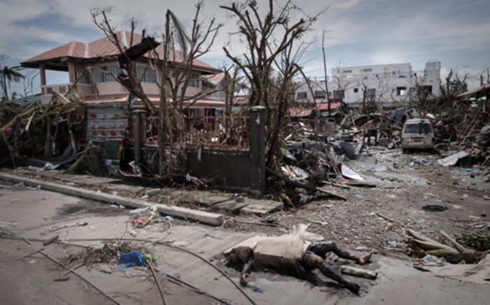 A dead body of a typhoon victim is left on the pavement of a street in Tacloban, on the eastern island of Leyte on 13 November 2013. Picture: Philippe Lope/AFP.
