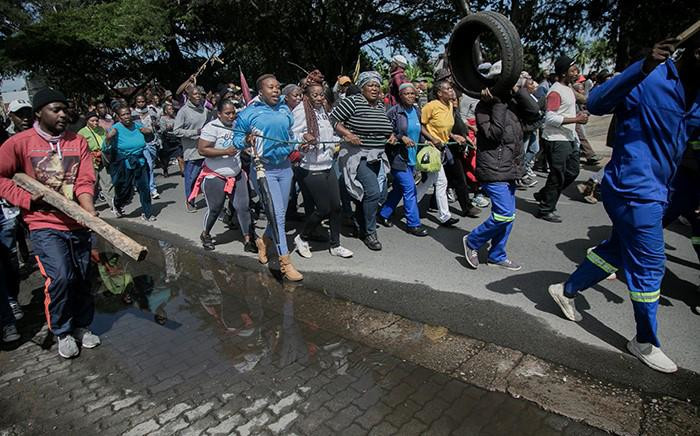 Protesting Alexandra residents on 8 April 2019 carry car tyres as they make their way to the City of Johannesburg local municipal offices. Picture: Sethembiso Zulu/EWN
