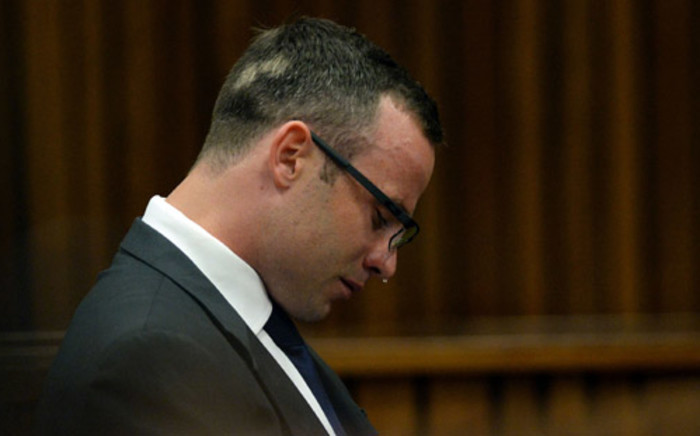 Oscar Pistorius weeps while listening to text messages given in evidence by cellphone analyst Francois Moller during his murder trial at the high court in Pretoria on 24 March 2014. Picture: Pool.