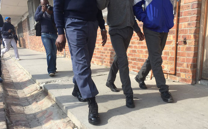 A police officer walks with two students at the Fezeka Secondary School during a search and seizure operation on 12 May 2016. Picture: Siyabonga Sesant/EWN.