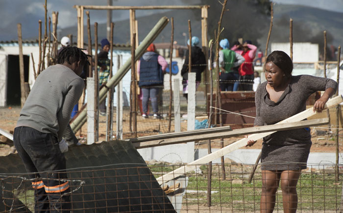 People take their building materials away as workers (not visible), break down uninhabited shacks in Bloekombos, Kraaifontein, in Cape Town on 6 August 2020. Picture: AFP