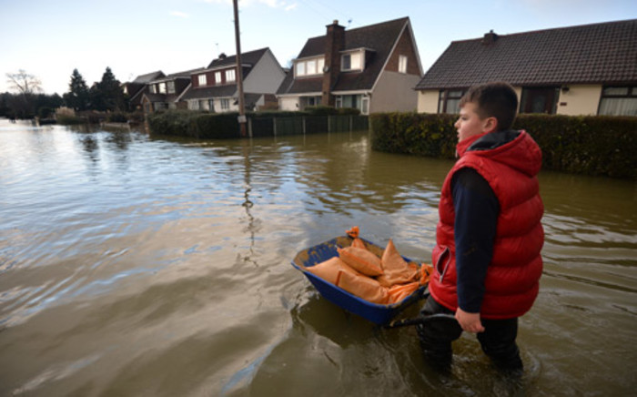 A boy pushes sandbags in a wheelbarrow along a flooded street in the village of Wraysbury in Berkshire, South East England, on 10 February, 2014. Picture: AFP.