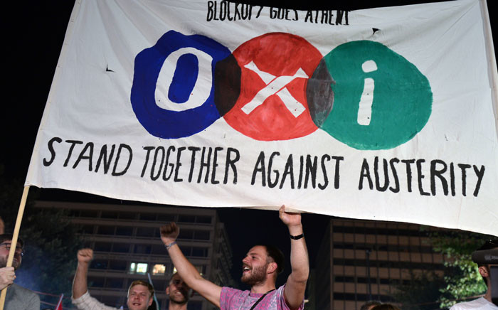 FILE: 'No' supporters hold a banner in front of the parliament late in Athens on 5 July 2015. Picture: AFP.