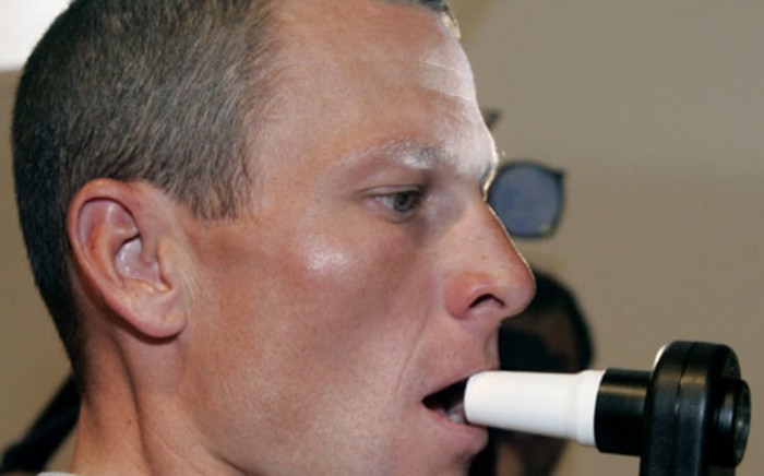 Lance Armstrong (US Postal/USA) blows in a tester during the traditional medical check-up on July 4, 2001 in Liege, Belgium, two days before the official start of the 91st Tour de France cycling race. Picture: AFP.
