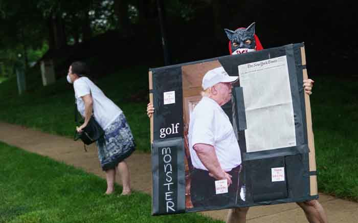 A protestor holds a placard outside of the Trump National Golf Course as US President Donald Trump departs in his motorcade in Sterling, Virginia on 24 May 2020. The placard includes a front page of the New York Times which lists some of those who have died from the coronavirus. Picture: AFP.