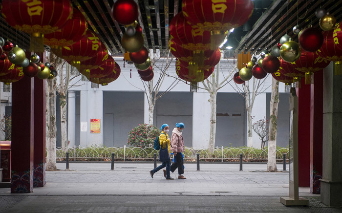 FILE: People wearing protective facemasks, amid fears of the spread of the COVID-19 novel coronavirus, walk on a street in Wuhan in China's central Hubei province on 27 February 2020. Picture: AFP.