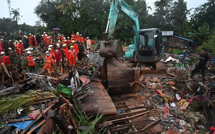 An excavator removes damaged structures after a landslide in Paung Township, Mon state on 10 August 2019. Picture: AFP