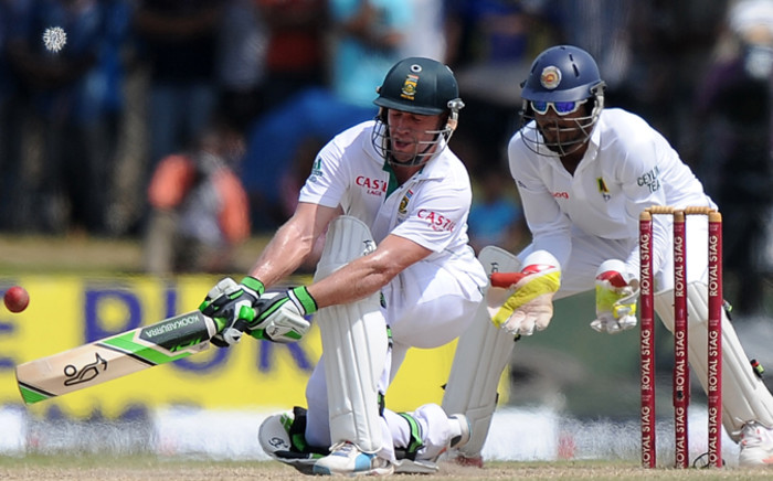 South Africa cricketer AB de Villiers (L) is watched by Sri Lankan wicketkeeper Dinesh Chandimal as he plays a shot during the fourth day of the opening Test match between Sri Lanka and South Africa at the Galle International Cricket Stadium in Galle on July 19, 2014. Picture: AFP.
