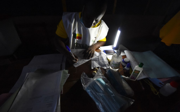 An official of the Autonomous National Electoral Commission (CENA) prepares before polls open at a polling station during the Benin Presidential election in Cotonou on 11 April 2021. Picture: AFP