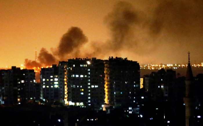Smoke billows from a Palestinian building following an Israeli air strike in Gaza City, on 18 July 2014. Picture: AFP.