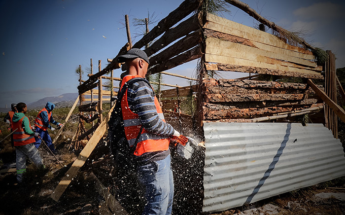 FILE: An eviction unit uses chainsaws and crowbars to demolish shacks. Picture: Thomas Holder/EWN
