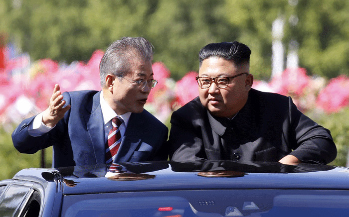 FILE: North Korean leader Kim Jong Un (R) listens to South Korean President Moon Jae-in (L) in an open-topped vehicle as they drive through Pyongyang on 18 September 2018. Picture: AFP