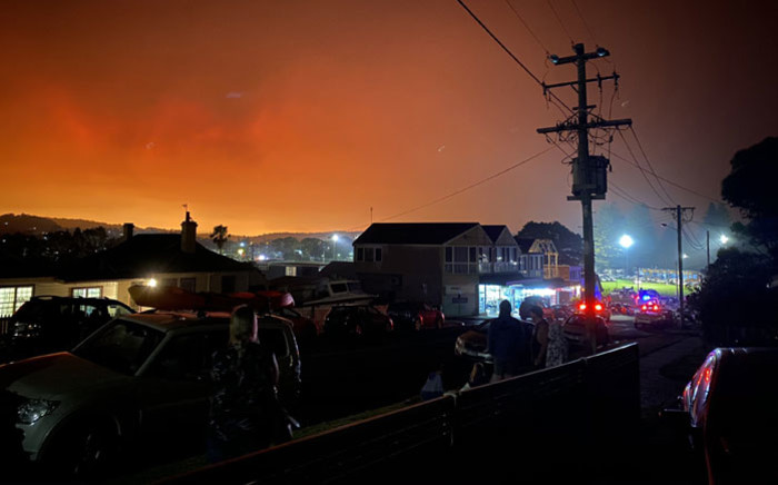 FILE: This handout photo received courtesy of Caitlin Nobes and taken on 31 December 2019 shows the darkened sky glowing orange from bushfires many kilometres away in Bermagui, Australia. Picture: AFP