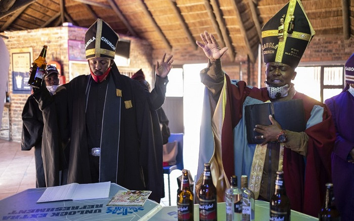 Tsietsi Makiti (R) the founder and leader of Gabola church gestures while praying during the Sunday sermon at Bunny's Tavern in Evaton on 30 August 2020. Picture: AFP