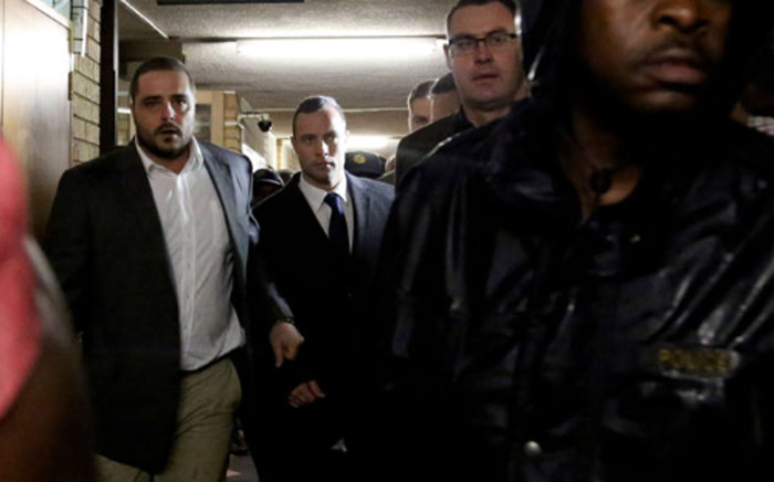 Oscar Pistorius is escorted into the High Court in Pretoria ahead of the second day of his murder trial on 4 March 2014. Picture: Sebabatso Mosamo/EWN.