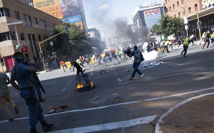 South African Police Service (SAPS) officers use teargas to disperse students during a protest in Braamfontein, Johannesburg, on March 10, 2021. Picture: Emmanuel Croset/AFP