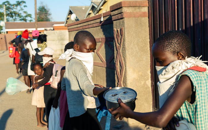 A queue of people with plates in hand forms outside Samantha Murozoki's home in Chitungwizaon on 5 May 2020, where she feeds the underprivileged a free meal during the government-imposed COVID-19 coronavirus lockdown period in Zimbabwe. Picture: AFP