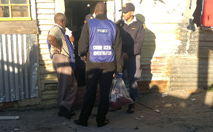 Crime scene investigators outside the shack in Village Heights where two children were found murdered on 13 June 2012. Picture: Janine Willemans/EWN