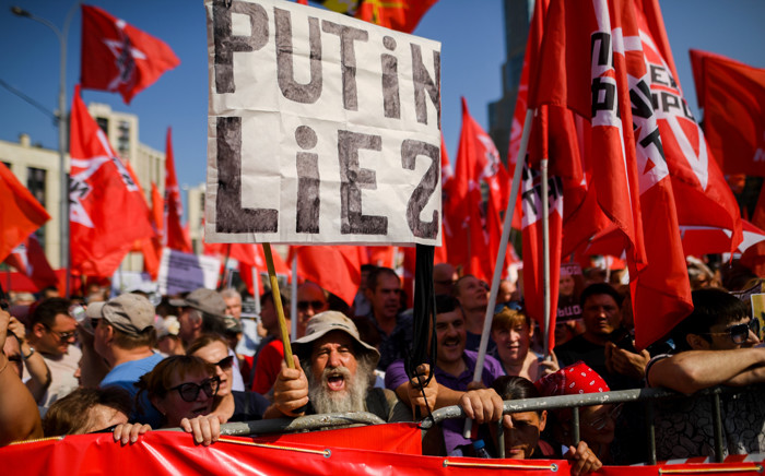 """FILE: A protester holds a placard reading """"Putin lies"""" during an opposition rally in central Moscow. Picture: AFP."""