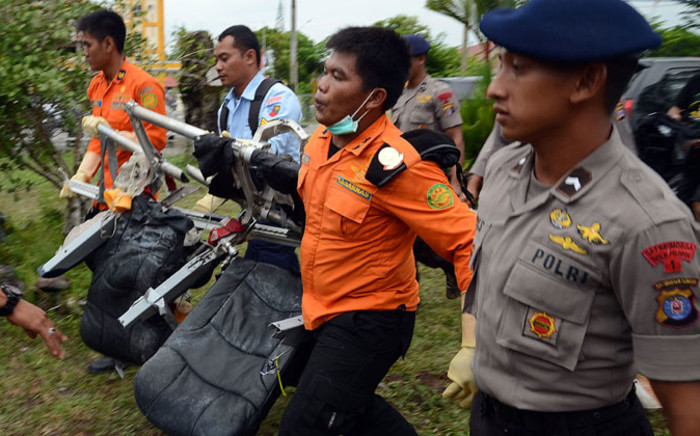 Members of an Indonesian search and rescue team carry passenger seats from the AirAsia flight 8501 in Pangkalan Bun on 5 January, 2015. Picture: AFP.